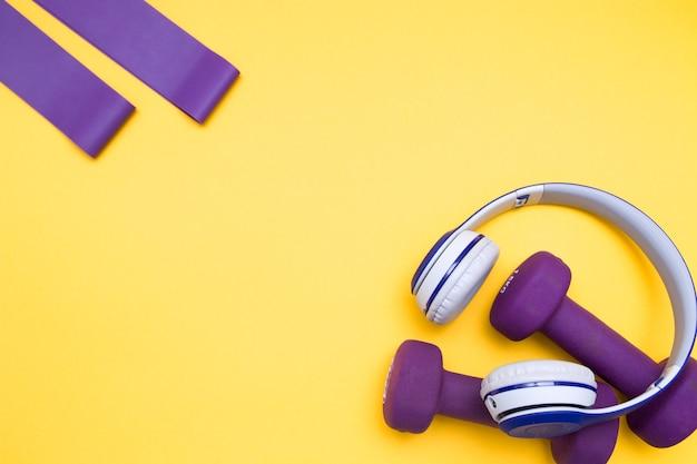 Słuchawki bezprzewodowe, gumki i fioletowe hantle na żółtym tle, miejsce na kopię, widok z góry