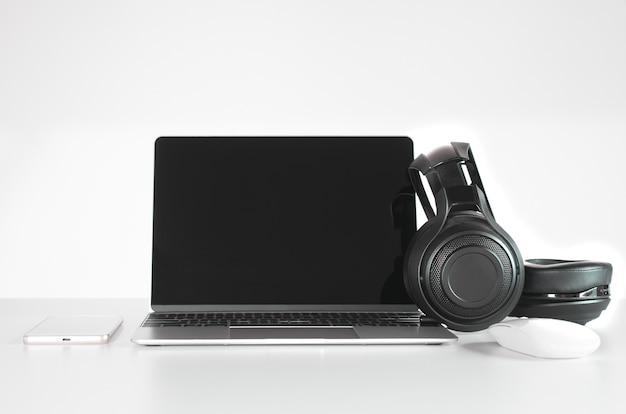 Słuchawki czarny, smartphone i laptop na biurko.