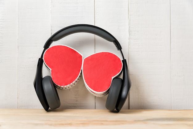 Słuchawki i dwa pudełka w kształcie serca. koncepcja serca piosenki.