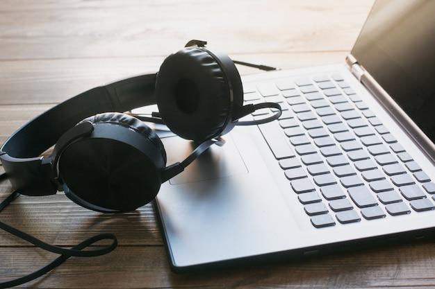 Słuchawki i klawiatura laptopa na desce.