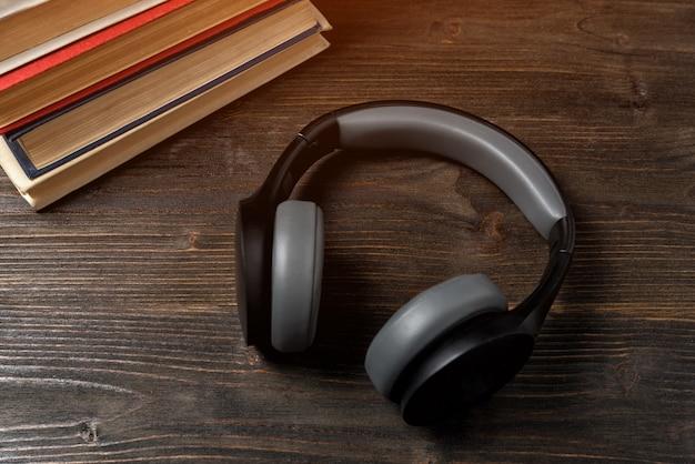 Słuchawki i książki na drewnianym tle. nauka z koncepcją audio.