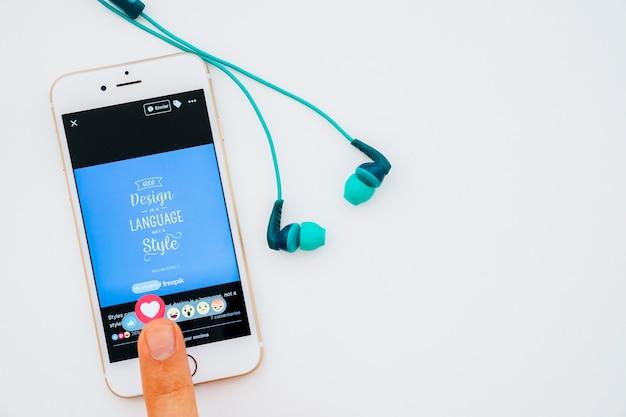 Słuchawki i palec naciskający jak buton na facebook