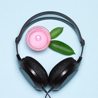 Słuchawki i płonąca świeca z zielonymi liśćmi. relaksująca muzyka z koncepcją dźwięków natury