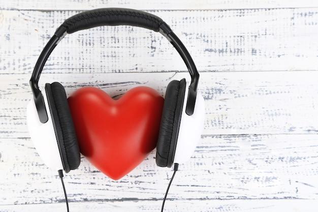 Słuchawki i serce na drewnianym stole