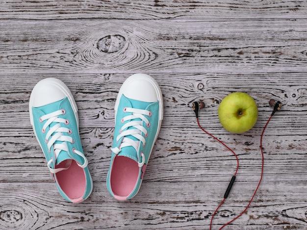 Słuchawki, jabłko i trampki na drewnianej podłodze. styl sportowy. leżał na płasko. widok z góry.