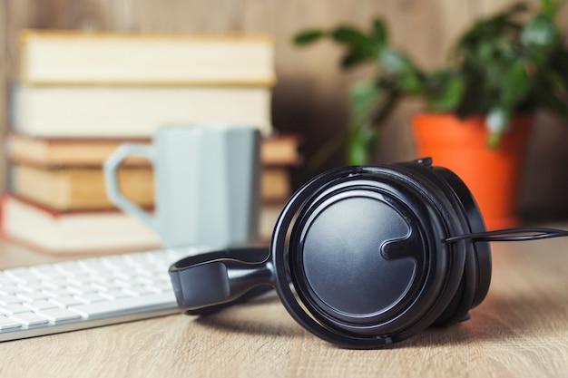 Słuchawki, klawiatura, stos książek i kubek na biurku. koncepcja biura, dzień pracy, wynagrodzenie godzinowe, harmonogram pracy, praca w call center.