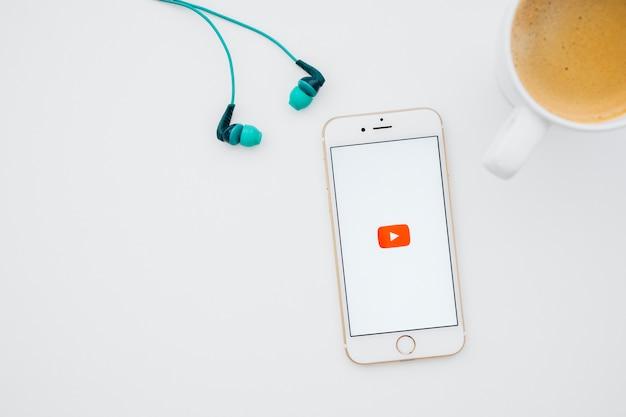 Słuchawki, kubek do kawy i telefon z youtube