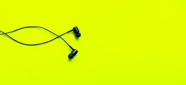 Słuchawki leżące na zielonym tle. koncepcja muzyki współczesnej. technologia audio.