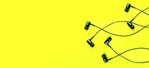 Słuchawki leżące na żółtym tle. koncepcja muzyki współczesnej. technologia audio.