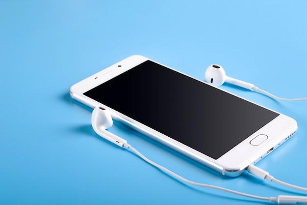 Słuchawki mobilne i telefon komórkowy w kolorze białym na niebieskim