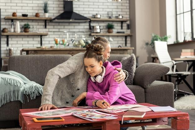 Słuchawki na karku. atrakcyjna urocza nastolatka nosząca białe słuchawki na szyi przytulająca ojca