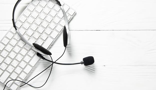 Słuchawki na klawiaturze komputera na białym stole