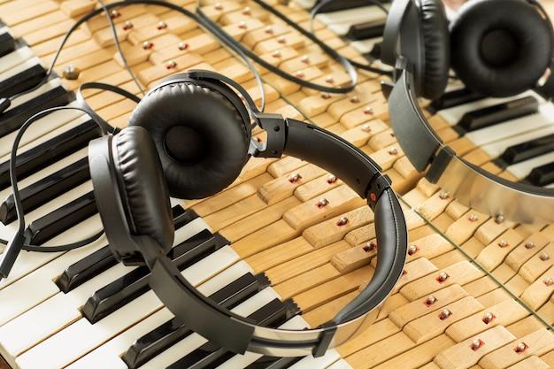 Słuchawki na klawiszach fortepianu, które odbijają się w lustrze