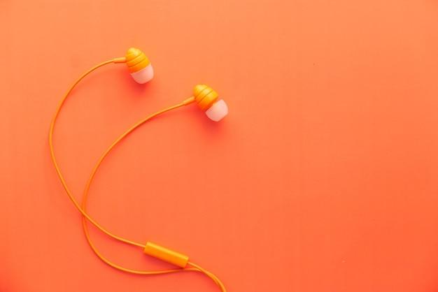 Słuchawki na pomarańczowym tle z miejsca na kopię