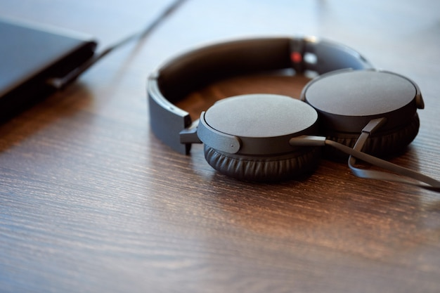 Słuchawki na stole biurowym. słuchawki podłączone do laptopa, miejsce. słuchanie muzyki w pracy