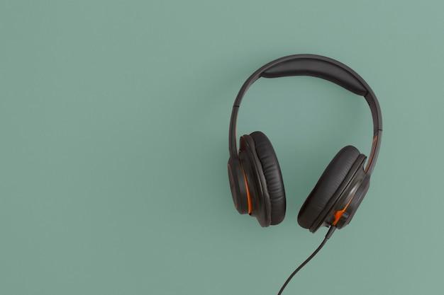 Słuchawki na zielonym tle. koncepcja muzyki. płaska kompozycja świecka. widok z góry.