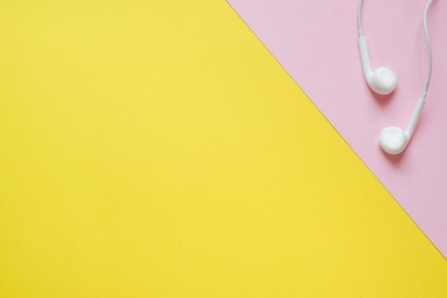 Słuchawki odtwarzacza na różowo-żółtym stole z kopią miejsca. koncepcja edukacji, szkoła i biuro