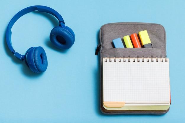 Słuchawki, otwarty zeszyt na torbie-piórniku z kolorowymi pisakami i markerem na niebieskim tle. widok z góry z miejsca na kopię. powrót do koncepcji szkoły. przybory szkolne.