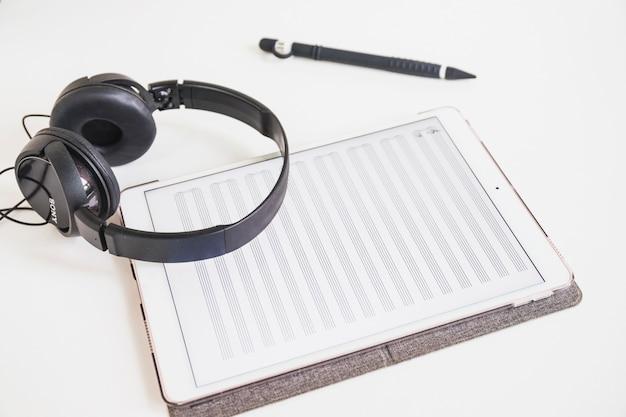 Słuchawki; rysik i graficzny cyfrowy tablet z nutą na ekranie na białym tle