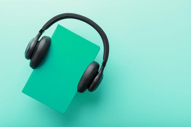Słuchawki są noszone na książce w niebieskiej twardej oprawie na niebieskim tle, widok z góry.