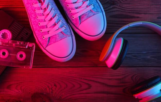Słuchawki stereo, kaseta audio i wideo, trampki na drewnianej powierzchni. neonowe światło czerwone i niebieskie