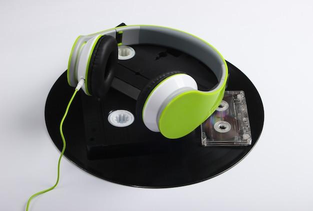 Słuchawki stereo, kasety wideo, płyty winylowe, kaseta audio na białej powierzchni