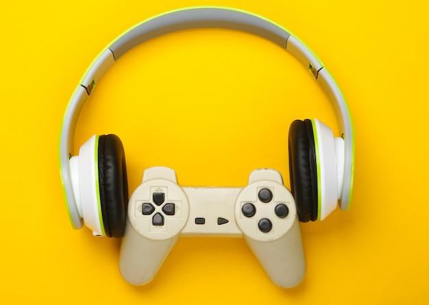 Słuchawki stereo z gamepadem na żółtej powierzchni