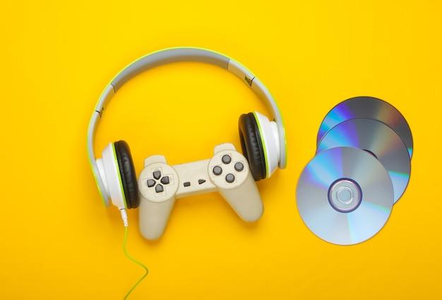Słuchawki stereo z gamepadem, płyty cd na żółtej powierzchni
