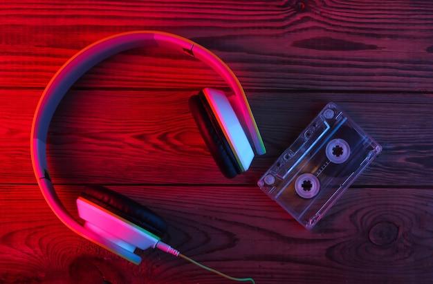 Słuchawki stereo z kasetą audio na drewnianej powierzchni. neonowe światło czerwone i niebieskie
