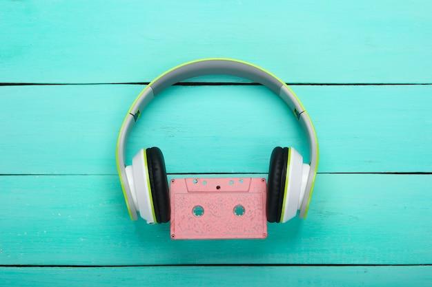 Słuchawki stereo z kasetą audio na niebieskim drewnianym stole