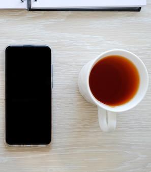 Słuchawki, telefon i herbata na stole.