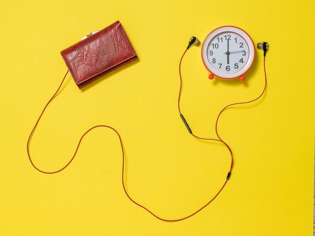 Słuchawki wystające z portfela i czerwony budzik. koncepcja podnoszenia tonu o poranku.