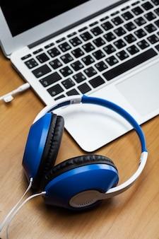 Słuchawki z laptopem na stole z bliska