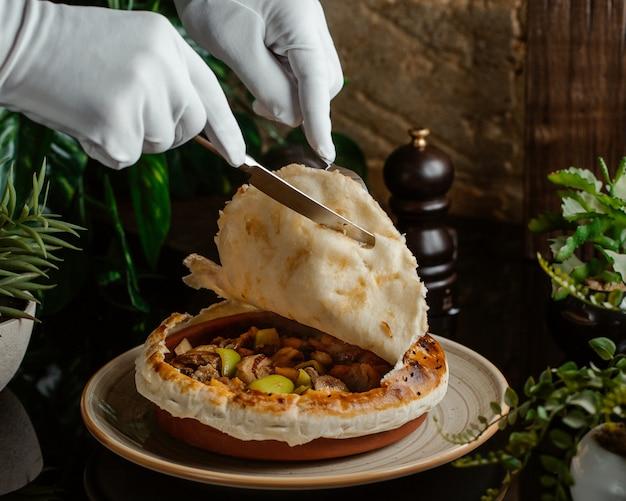 Sługa rozcinający górną część ciasta mięsnego zapakowany w ceramiczny kubek