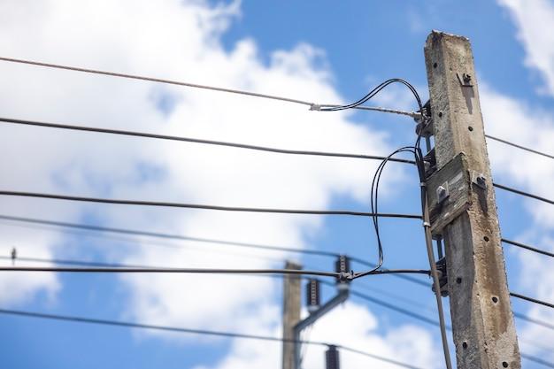 Słup elektryczny i linia energetyczna w pogodny dzień z błękitnym niebem i białymi chmurami w tle.