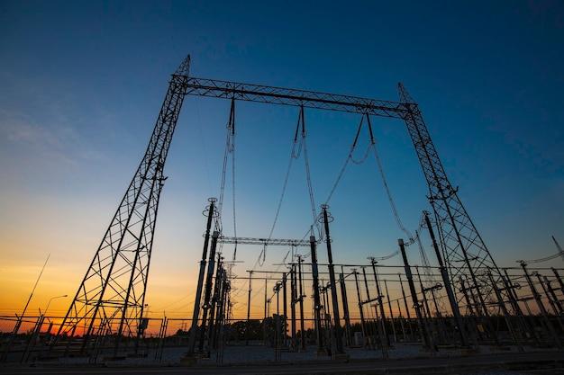 Słup elektryczny wysokiego napięcia i linie przesyłowe w godzinach wieczornych. słupy energii elektrycznej o zachodzie słońca. moc i energia