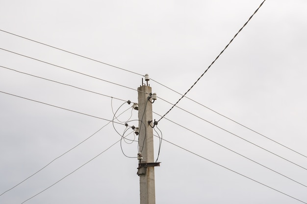 Słup elektryczny z linią przewodów zasilających w pochmurny dzień