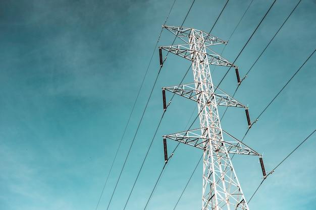 Słup energii elektrycznej przeciw błękitne niebo chmury, linii przesyłowej energii elektrycznej na obszarach wiejskich, słup wysokiego napięcia energii elektrycznej na tle jasnego nieba chmury, pylon transmisji elektrycznej