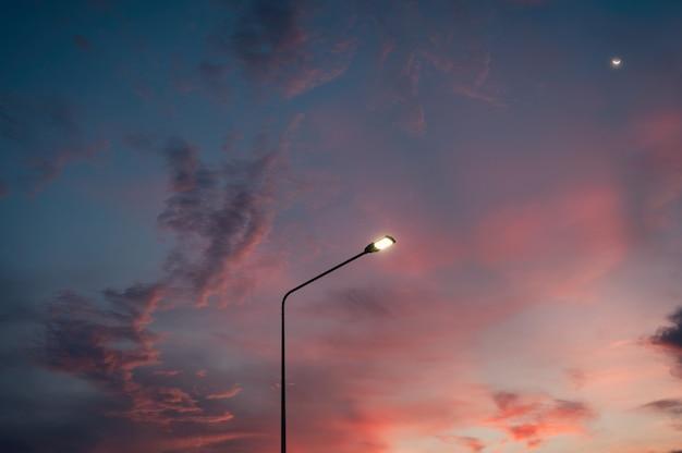 Słup latarni ulicznej z księżycem i kolorowym wieczornym niebem