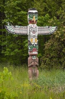 Słup totemu w zieleni w stanley park niedaleko vancouver w kanadzie