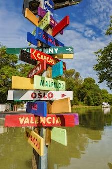 Słupek ze znakami wskazującymi kierunek różnych miast w żywych kolorach