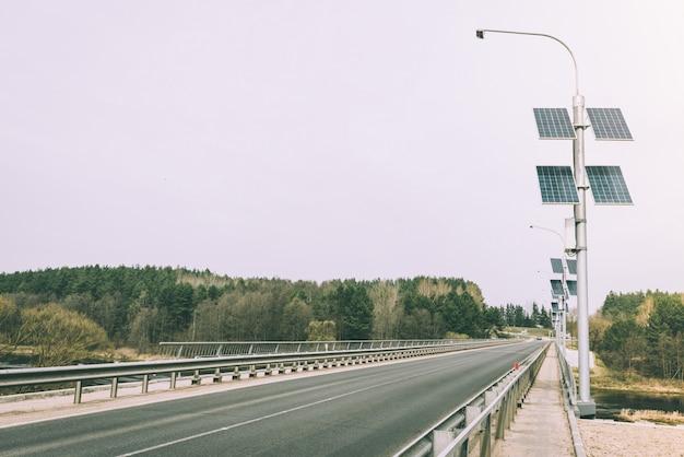 Słupy do lamp ulicznych zasilane energią słoneczną. panele słoneczne na słupie elektrycznym do oświetlenia drogi w mieście na moście.