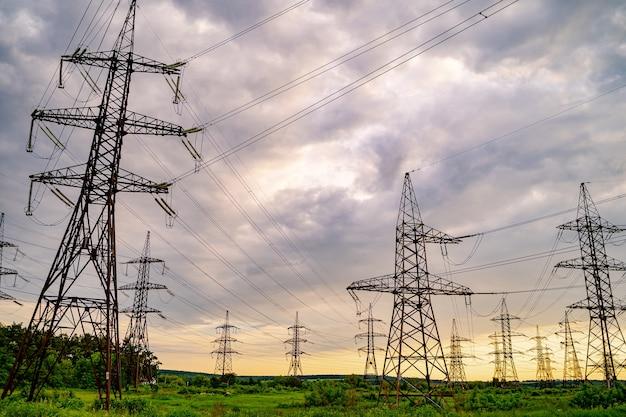 Słupy elektryczne i linie wysokiego napięcia na zielonej trawie. elektrownia. sieć energetyczna. widok z dołu.