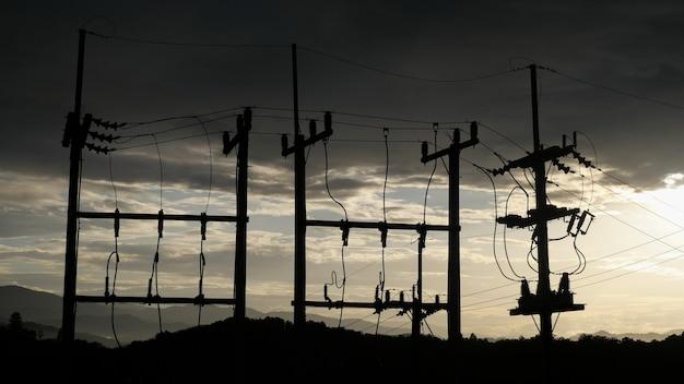 Słupy Elektryczne Kontrastują Z Niebem O Zachodzie Słońca Wieczorem. Premium Zdjęcia