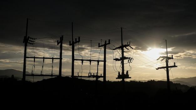 Słupy elektryczne kontrastują z niebem o zachodzie słońca wieczorem.