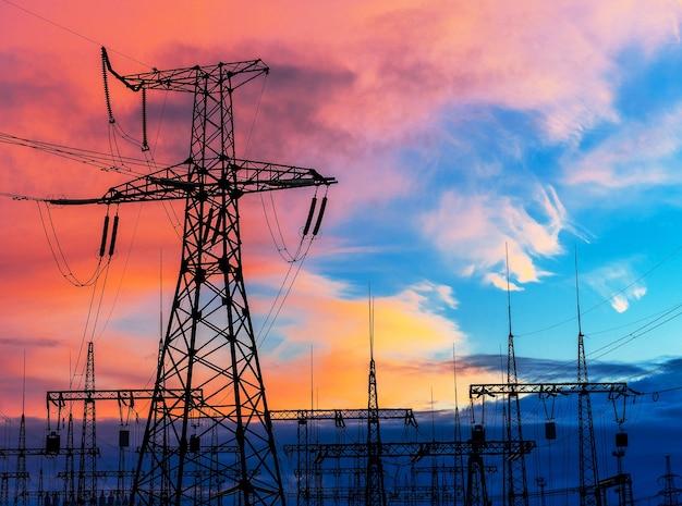 Słupy elektryczne nad podstacją transformatorową podczas zachodu słońca.