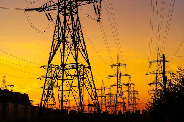 Słupy elektryczne przenoszące zasilanie w wiejskim krajobrazie podczas zachodu słońca