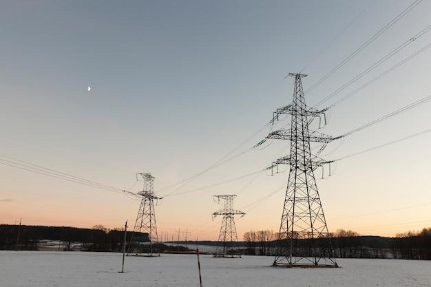 Słupy elektryczne sfotografowane w sezonie zimowym. na ziemi występują zaspy śnieżne po opadach śniegu. niebo w tle o zachodzie słońca
