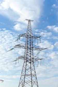 Słupy elektryczne ustawione w ciągu dnia, chmury na niebie, budynki przemysłowe