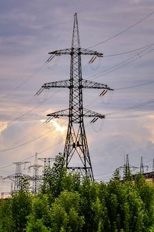 Słupy energetyczne niosące zasilanie w wiejskim krajobrazie podczas zachodu słońca. selektywne skupienie.